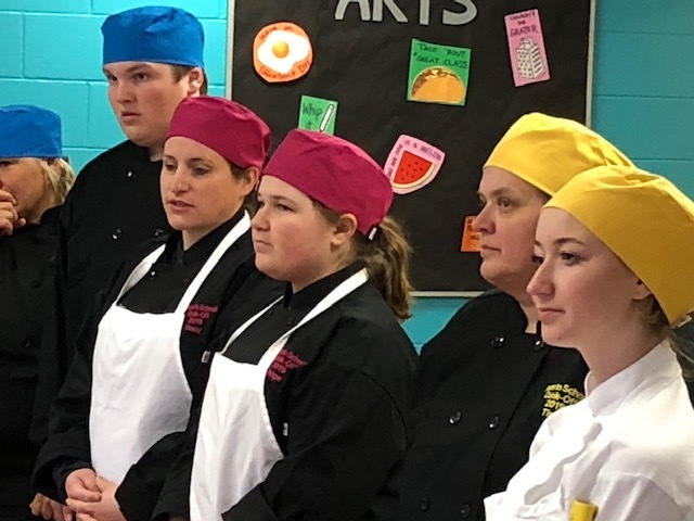 student and staff in chef outfits